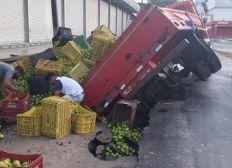 Caminhão carregado com laranja fica preso em cratera após piso ceder